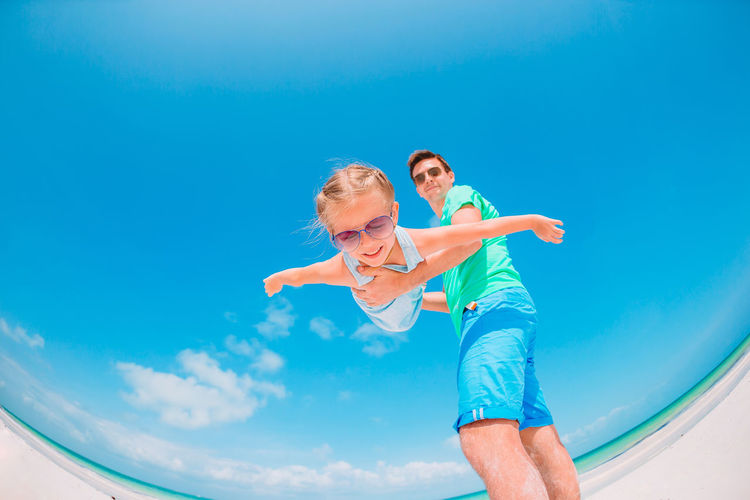 Low angle view of father holding daughter against sky