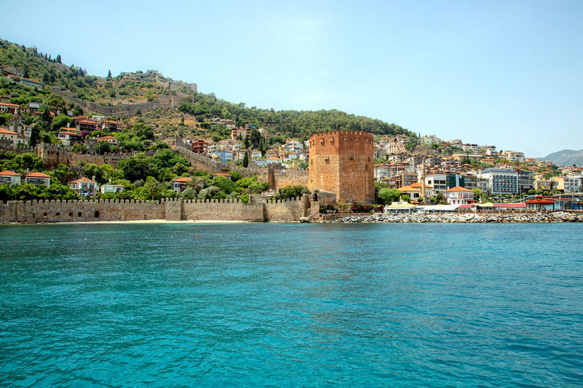 Red Tower Alanya Historical Building Historical Sights Turkey Vacation Time Architecture Blue Building Building Exterior Built Structure City Mountain Range Nature Port Red Tower Residential District Sea Sky Town TOWNSCAPE Travel Destinations Turquoise Colored Vacation Destination Water Waterfront