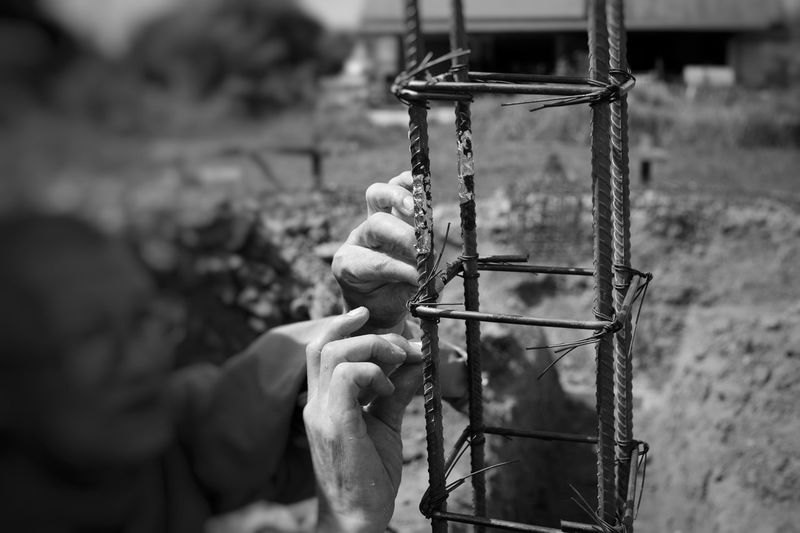 Monochrome picture of unidentified monk posting the golden leaf on the reinforcement steel in the praying ceremony for luck and safety in construction of new support and religion concept Vintage Art Priest Monk  Structure Black And White Picture Monochrome Construction Site Luck Belief Religion Steel Reinforcement Focus On Foreground Day Close-up No People Metal Outdoors Chain Land Pattern Tied Up Sunlight Creativity