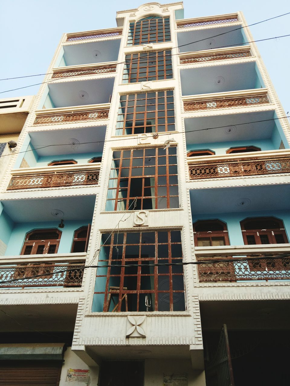 architecture, building exterior, window, low angle view, built structure, balcony, air conditioner, no people, residential building, apartment, city, outdoors, day, modern, residential