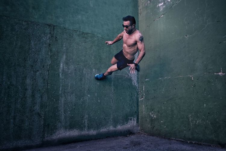 Full length of shirtless man jumping in concrete wall