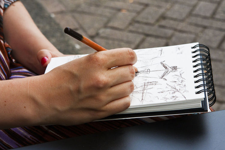 Cropped Hands Of Woman Drawing On Book