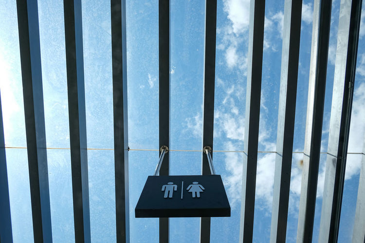 Low angle view of restroom sign hanging from pattern roof