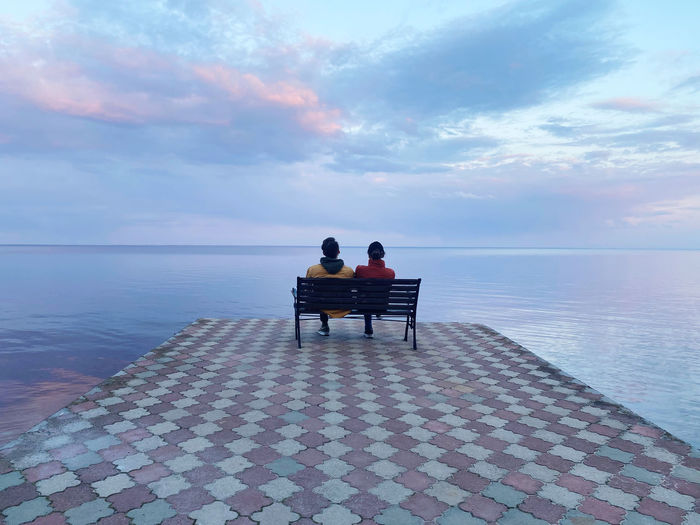 Rear view of men sitting on bench looking at sea against sky