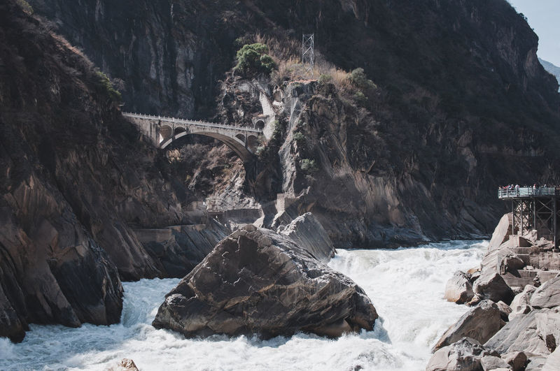 Low angle view of bridge by rock formation over river