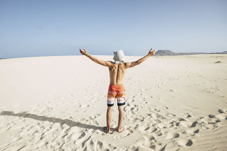 young teenager caucasian male enjoy the freedom and the holiday vacation standing with open arms at the beach in the desert dunes. mountain in background. happiness concept Land Sand Sky One Person Beach Leisure Activity Lifestyles Rear View Human Arm Nature Real People Full Length Holiday Vacations Trip Standing Beauty In Nature Day Clear Sky Limb Arms Raised Arms Outstretched Freedom Shorts Teenager Boy