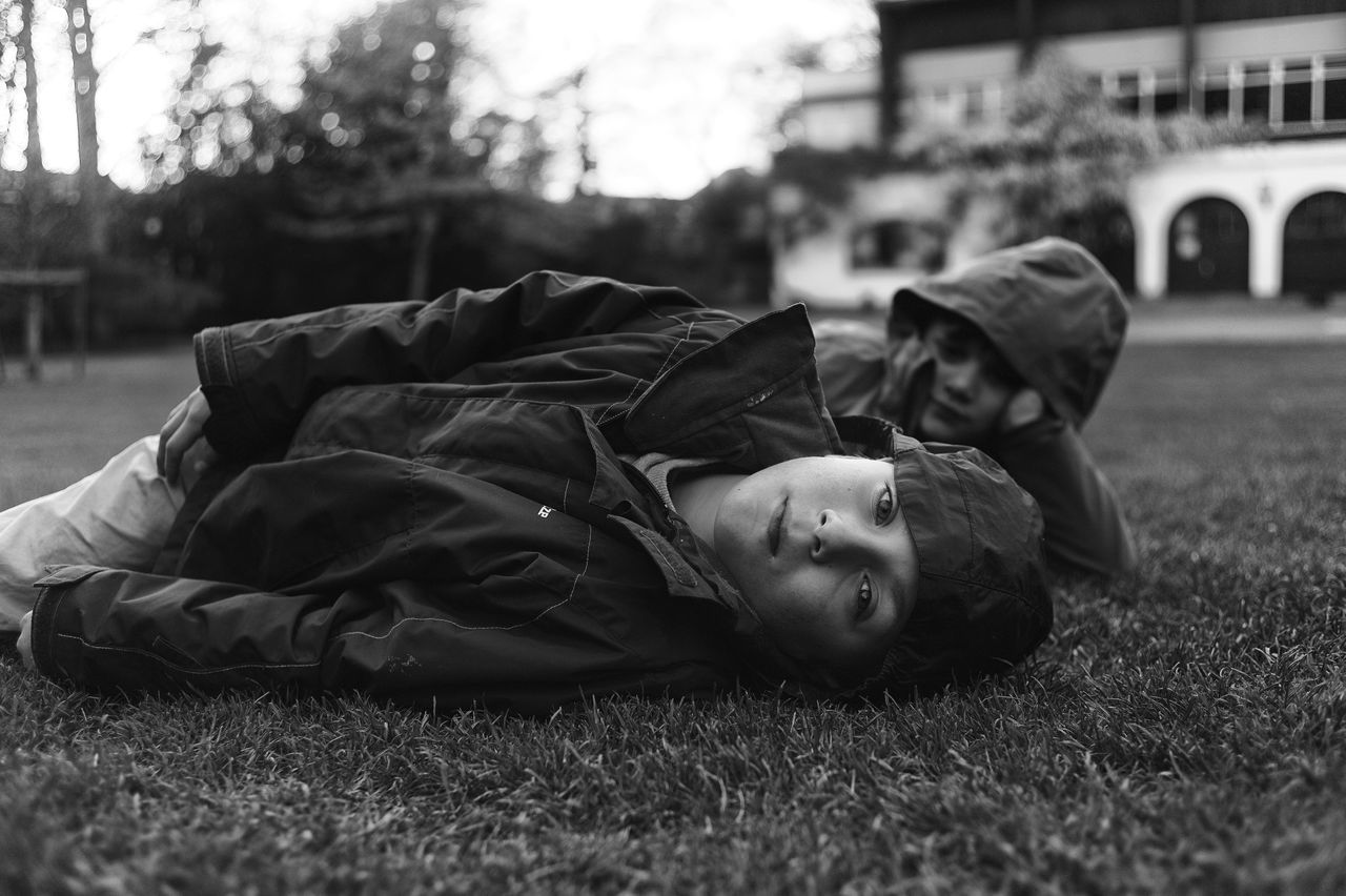 SIDE VIEW OF BOY SLEEPING IN GRASS