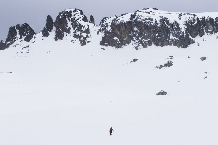 Hiker Walking On Snow Covered Field By Mountains