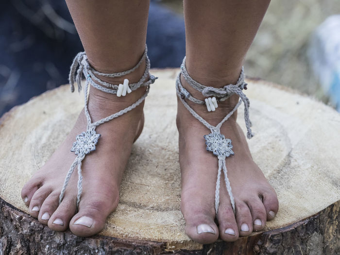 Low section of woman wearing anklet on tree stump