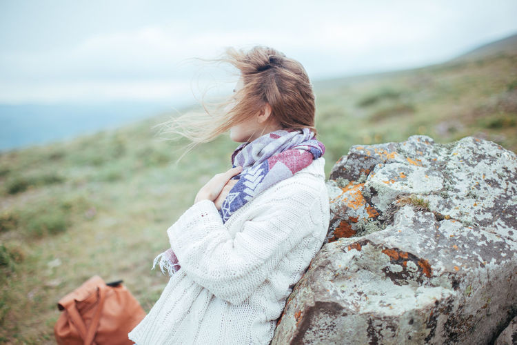 Woman leaning against rock