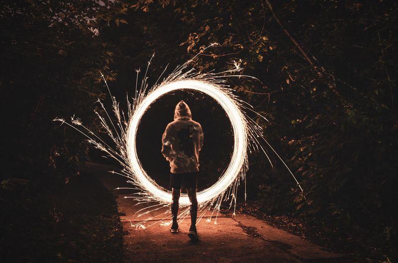 Man standing on illuminated ferris wheel at night