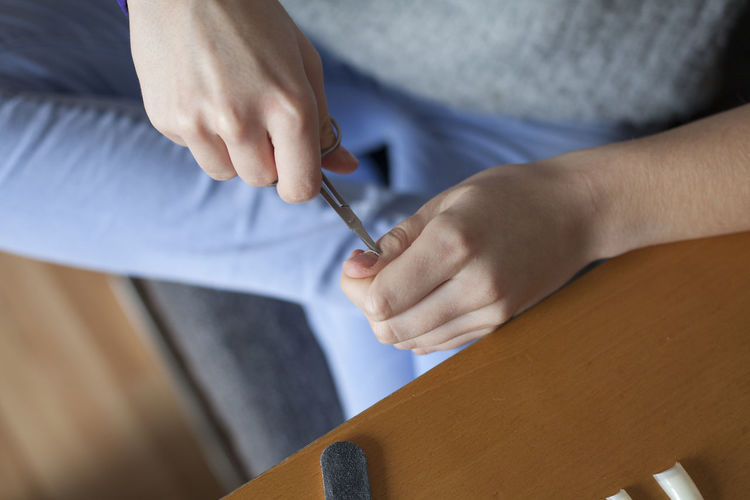 Midsection of woman cutting fingernails