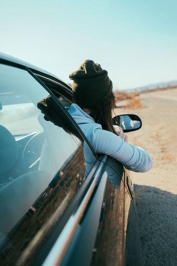 Side view of woman peeking through car window