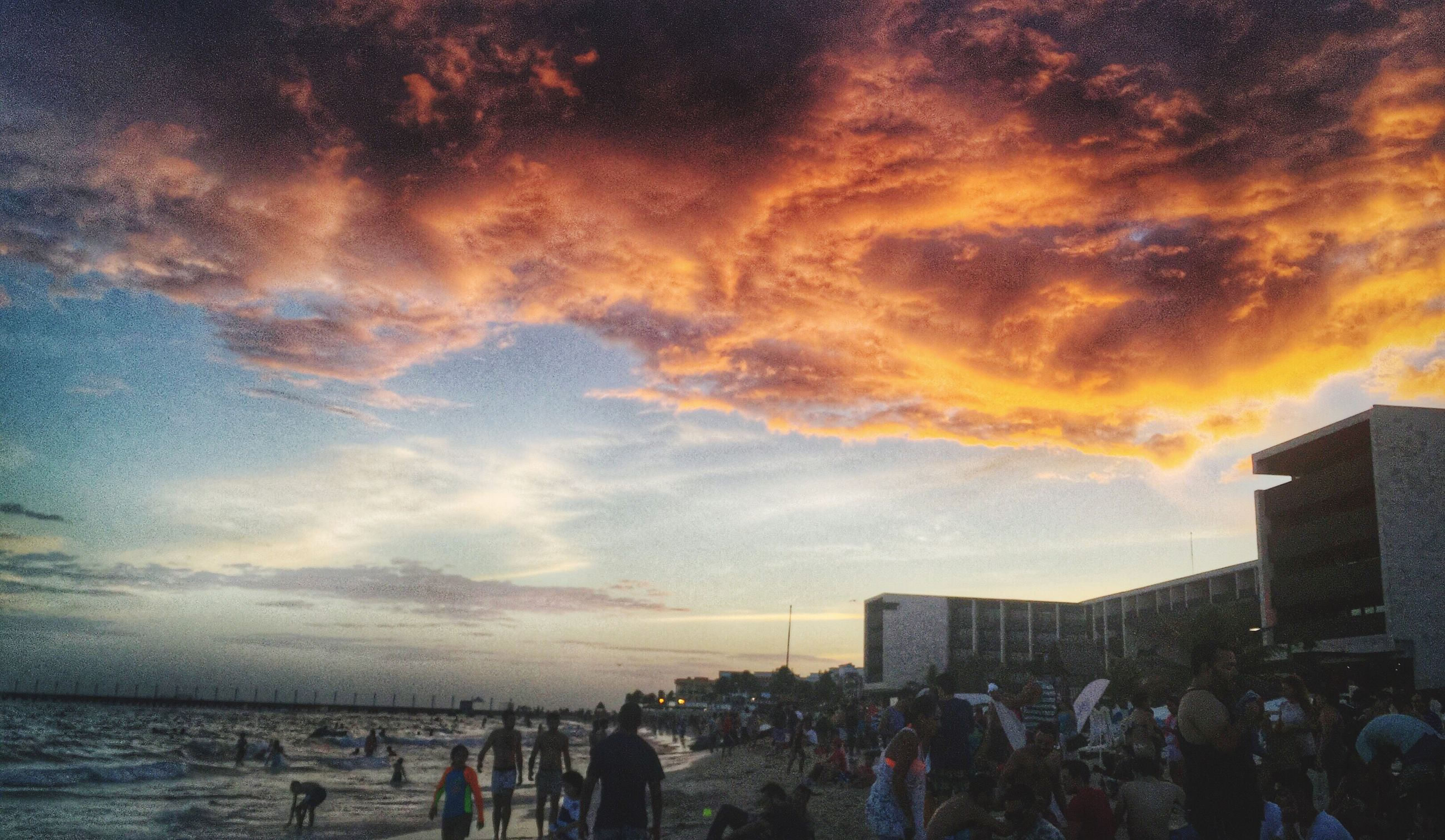 sky, sea, sunset, cloud - sky, large group of people, water, building exterior, beach, lifestyles, built structure, architecture, leisure activity, person, men, horizon over water, cloudy, cloud, city, silhouette