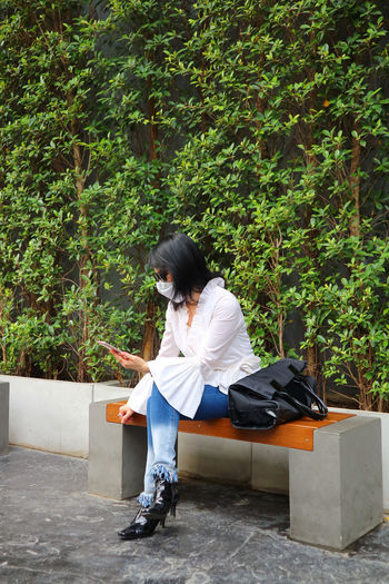Woman sitting on seat against plants