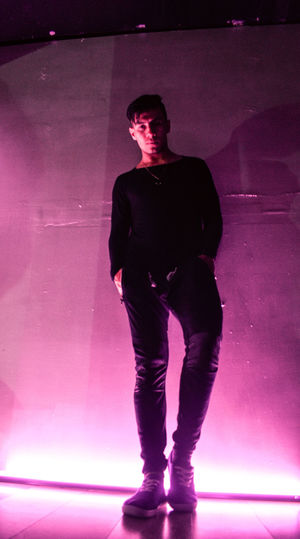 Full length portrait of young man standing against illuminated wall