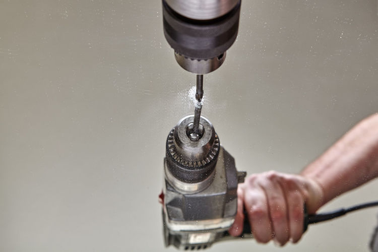 Close-up of hand holding faucet against water