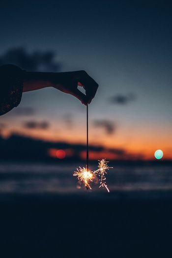 Cropped hand of woman holding illuminated sparklers during sunset