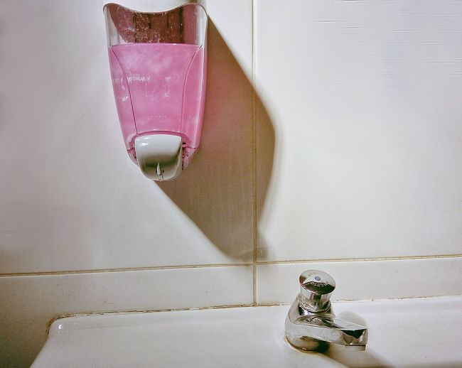Soap dispenser mouthed on wall by sink in bathroom