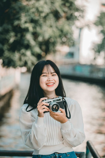 Portrait of smiling young woman holding camera standing by canal