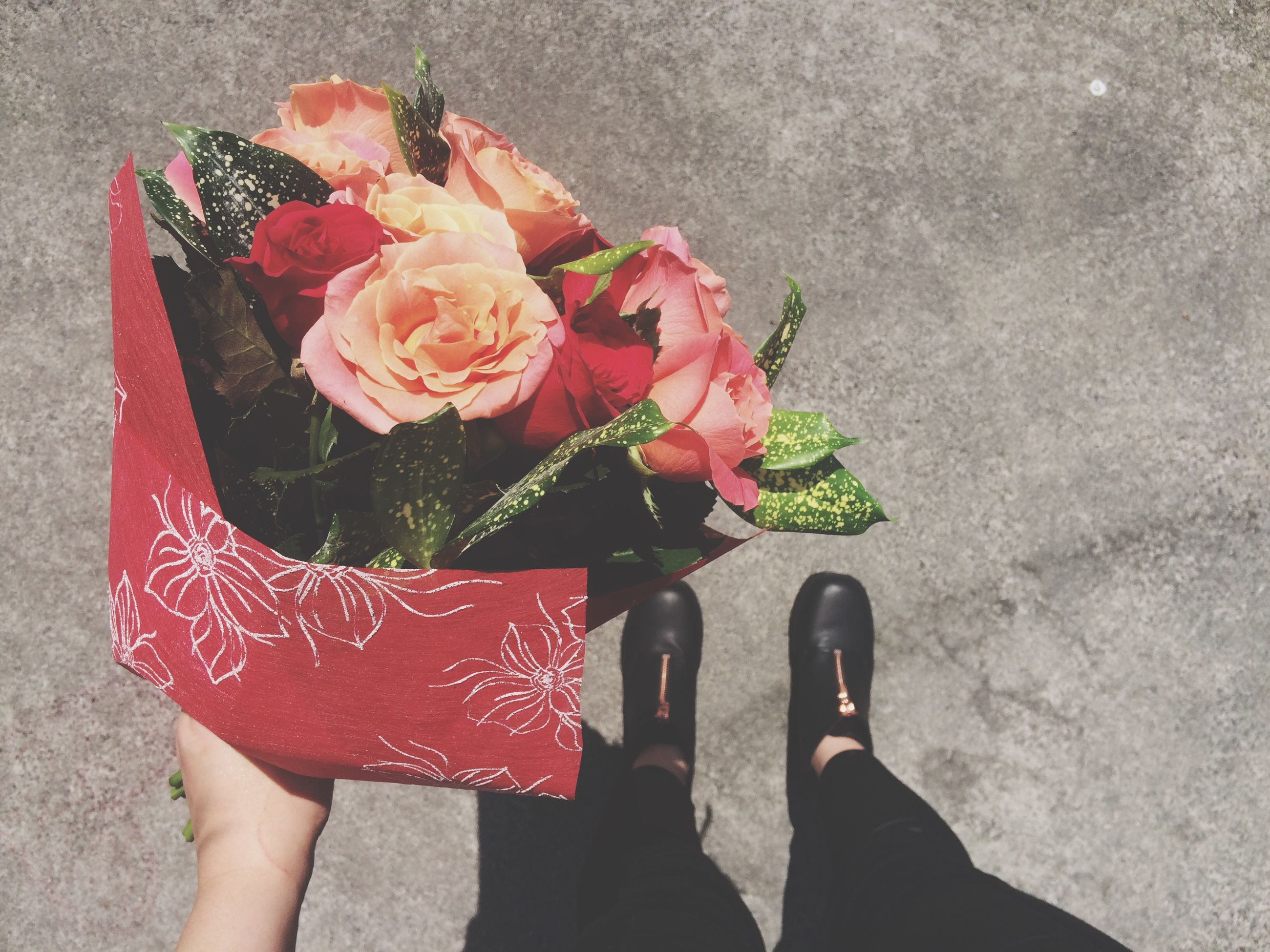 flower, personal perspective, high angle view, holding, low section, petal, freshness, red, lifestyles, person, leisure activity, standing, pink color, fragility, unrecognizable person