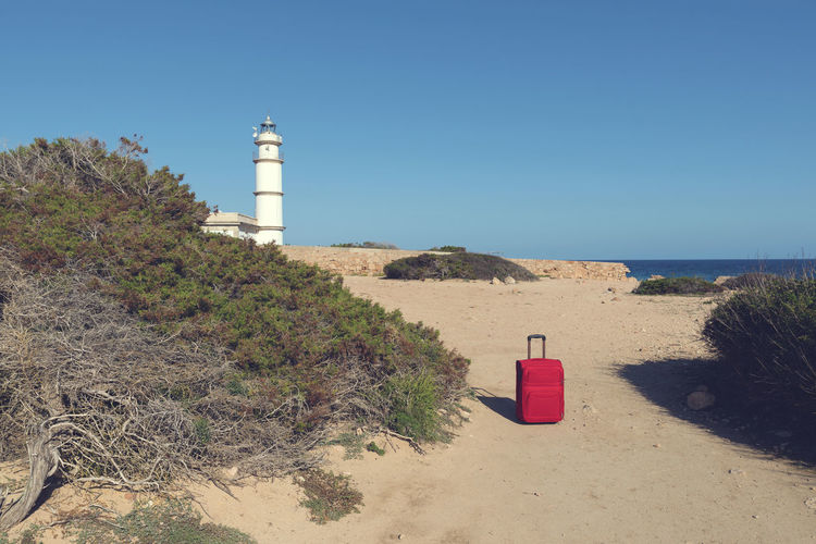 Red suitcase on a path to lighthouse at Cap de ses Salines. Selective focus Escaping Holiday Light Lighthouse Mediterranean  Red Rocky Coastline Soft Travel Trip Vacations Wanderlust Blue Destination Journey Leisure Activity Luggage No People Packing Sea Stone Suitcase Summer Tourism Water