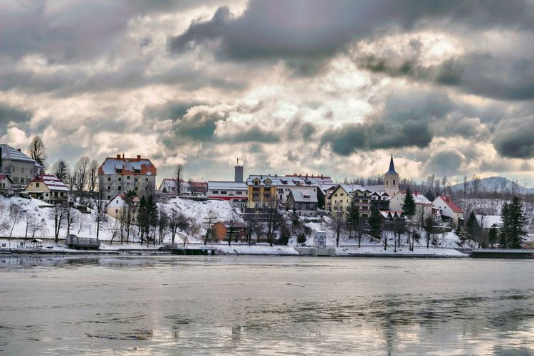 Buildings by river against sky in city during winter