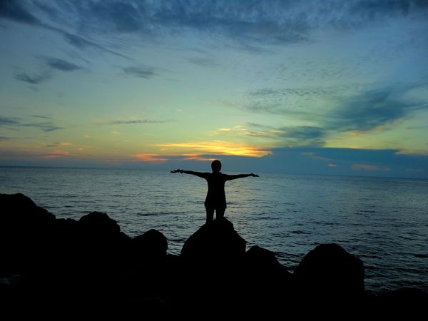 Singing the songs of the ocean. Reflection Sunset Nature Sky Silhouette Outdoors Beauty In Nature Travel Travel Destinations Oceanside One Person Shadows & Lights Facing The Ocean Arms Wide Open Silouette & Sky Camiguin Philippines Finding New Frontiers The Great Outdoors - 2017 EyeEm Awards Live For The Story An Eye For Travel