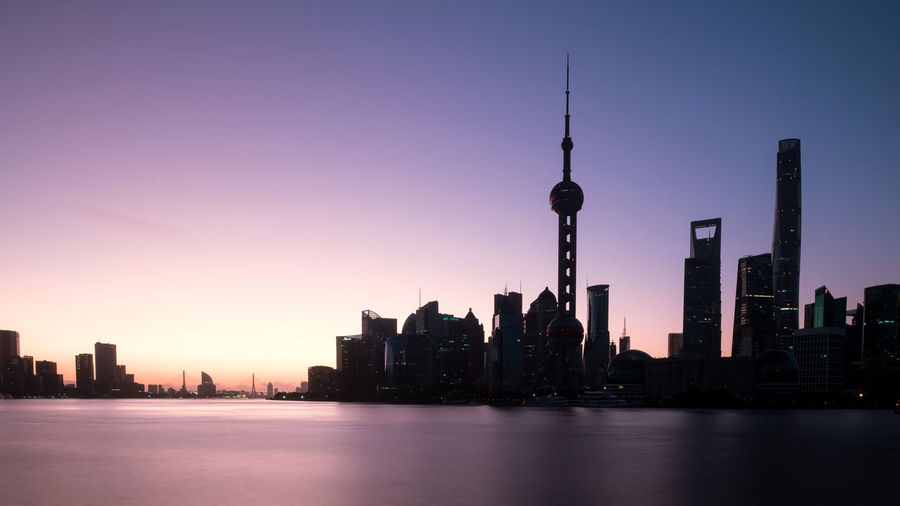 Oriental pearl tower by huangpu river in city during sunset