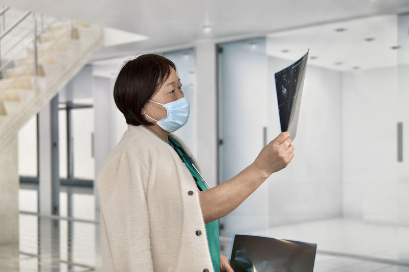 Nurse examining x-ray at hospital