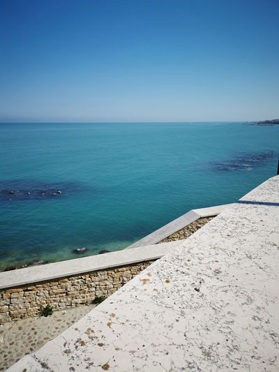 Scenic view of sea against clear blue sky. stairs connected from road to sea.