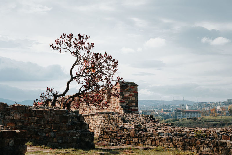 Old ruins and buildings against cloudy sky