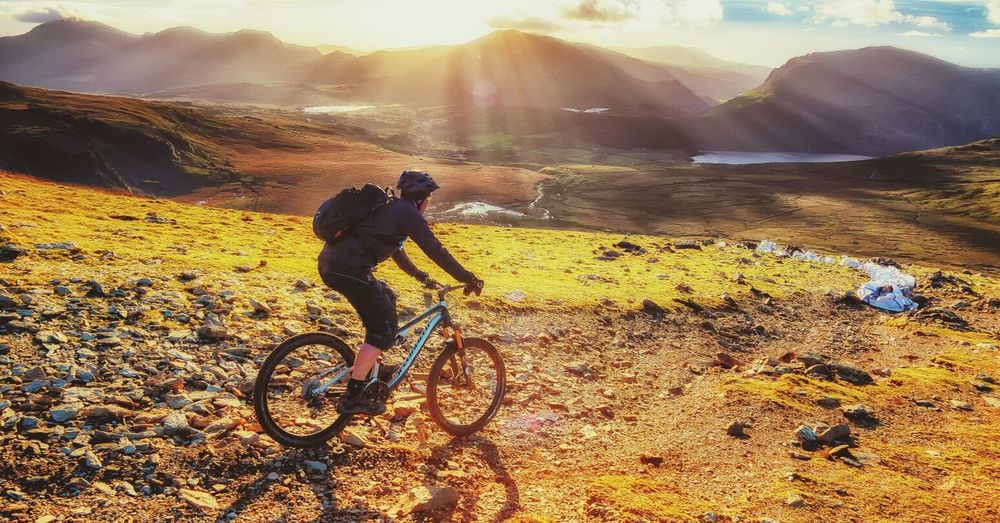 Side view of person riding bicycle on hill during sunny day