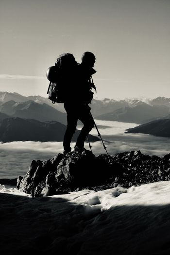 Silhouette man hiking on snowcapped mountain against sky