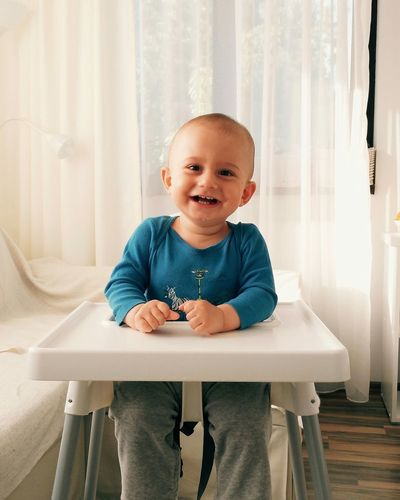 Cheerful baby sitting on high chair at home