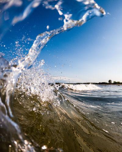 Close-up of waves splashing on beach against sky