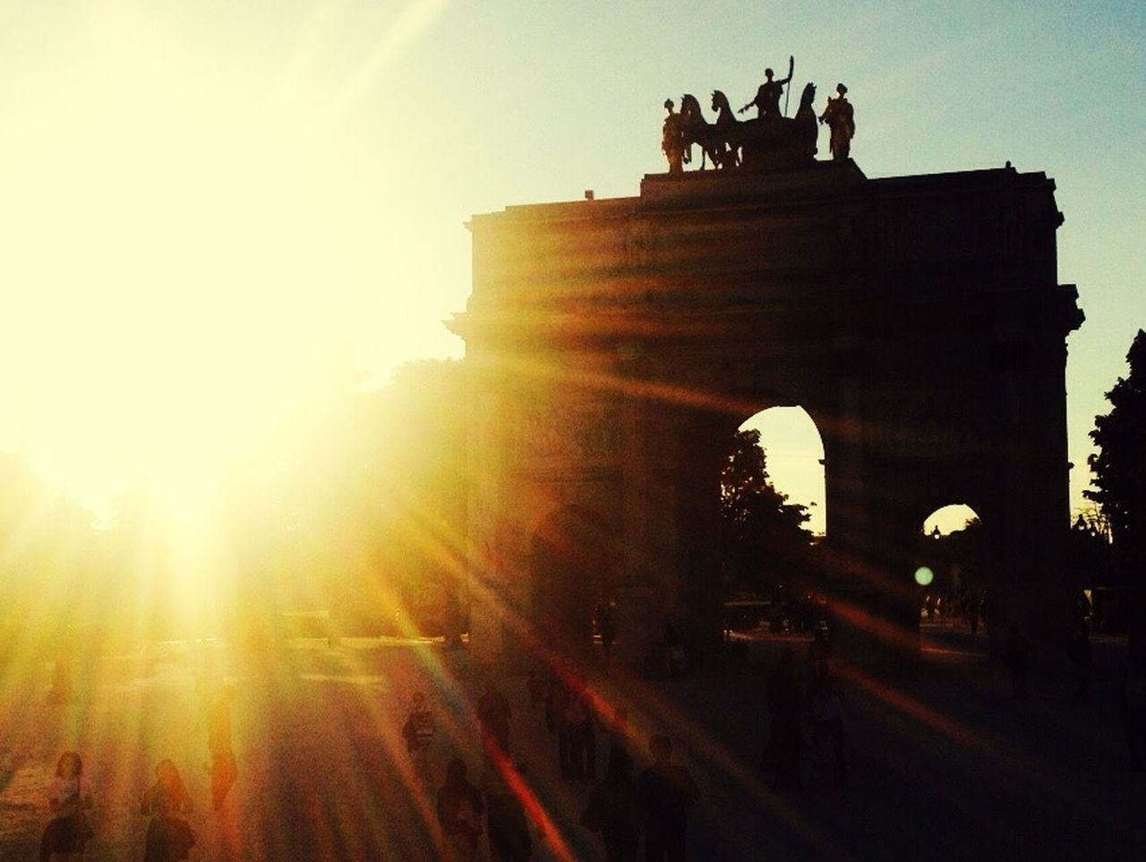 history, architecture, built structure, sun, travel destinations, lens flare, tourism, silhouette, sunlight, outdoors, low angle view, travel, sunset, triumphal arch, sky, statue, large group of people, city gate, ancient, day, men, sculpture, real people, building exterior, people