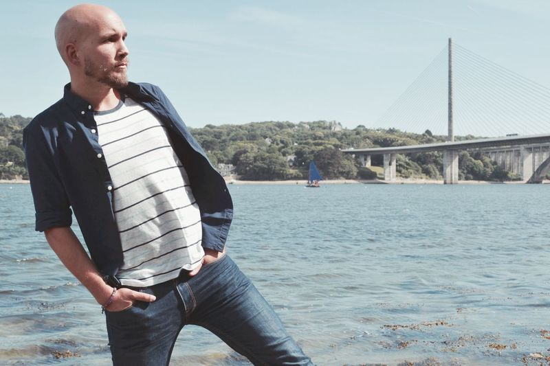 Man on bridge over river against sky