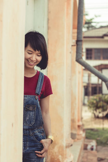 Happy of woman with hand on hip standing outside house