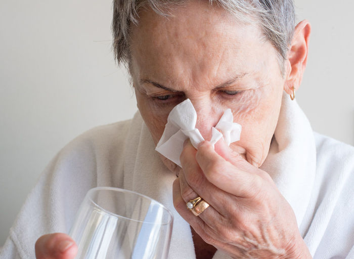Older woman blowing nose and holding glass of water Woman Adult Adults Only Blowing Cleaning Close-up Cold Temperature Day Facial Tissue Headshot Healthcare And Medicine Holding Home Interior Human Body Part Human Hand Human Nose Illness Indoors  Lifestyles Mature Adult Nose One Person People