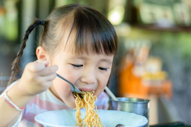Portrait of cute girl eating noodles at restaurant