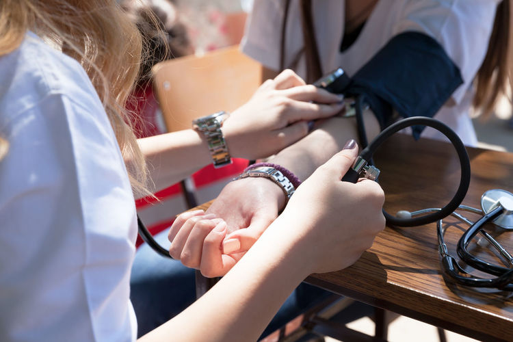 Cropped image of doctor checking blood pressure of patient