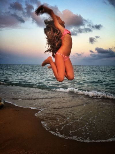 Woman Jumping At Beach During Sunset