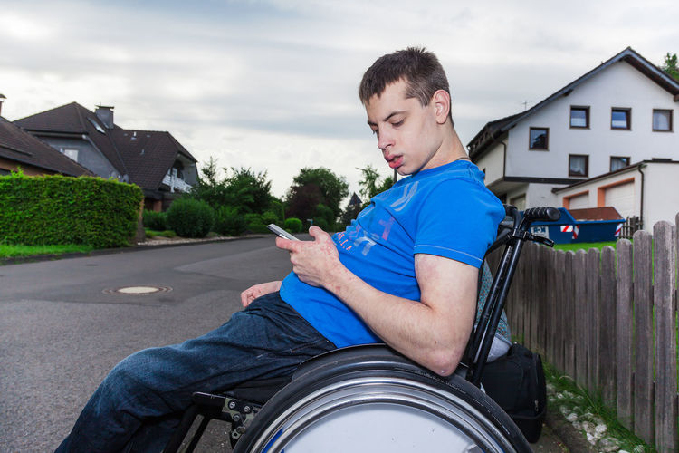 Disabled of man using mobile phone while sitting on wheelchair