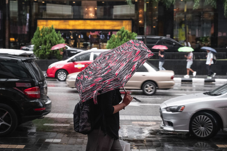Man with umbrella on road in rainy season at bukit bintang kuala lumpur