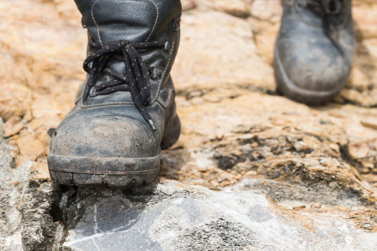 Trekking leather boot on the rock Low Section Human Body Part Shoe Boot One Person Human Leg Body Part Day Black Color Outdoors Focus On Foreground Close-up Nature Human Foot Working Dirt Unrecognizable Person Solid Protection Leather Dirty Mud Lace - Fastener