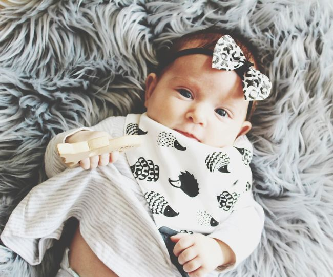 Portrait of cute baby lying on bed at home. monochrome colours, bow, hedgehogs bib, wooden teether.
