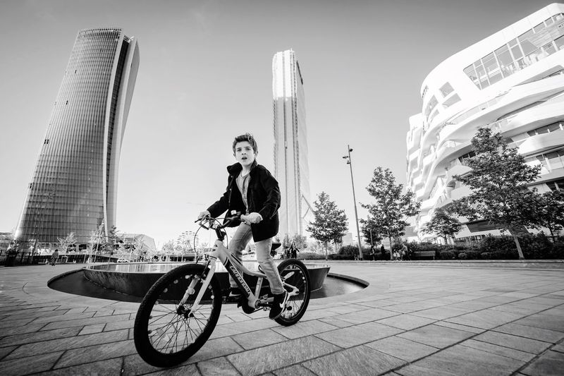 Citylife / Milano Built Structure Two People Architecture Real People Outdoors Casual Clothing Full Length Lifestyles City Leisure Activity Togetherness Travel Destinations Day Riding Sky Clear Sky Vacations Portrait Italy Skyscraper Bike Wide Angle Streetphotography