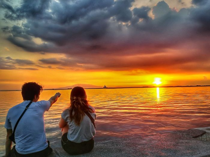 Together at Sunset Travelling Young Man Young Woman Couple Manila, Philippines Baywalk Roxas Boulevard Dramatic Sky Water Sea Togetherness Sunset Friendship