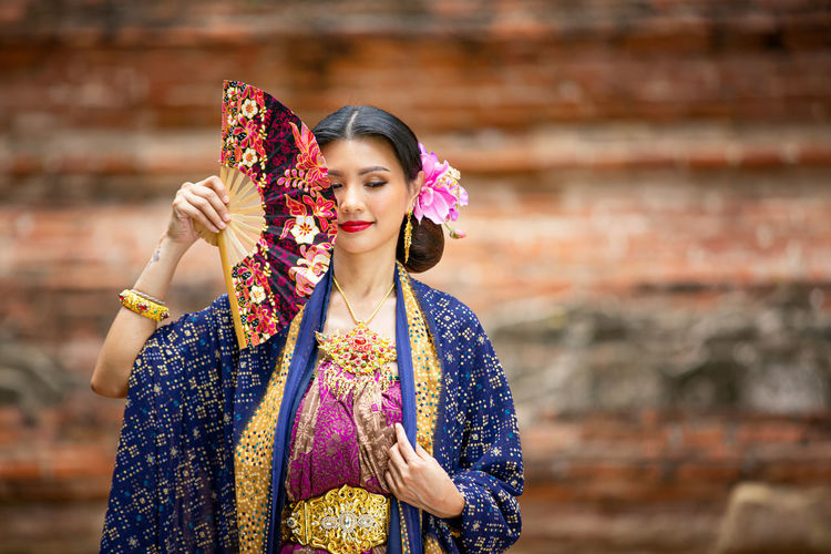 Woman in traditional clothing standing outdoors